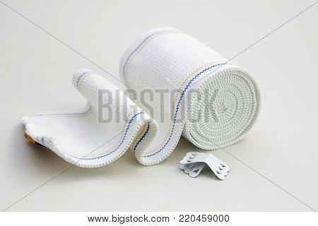 A roll of elastic bandage for sprains on white background