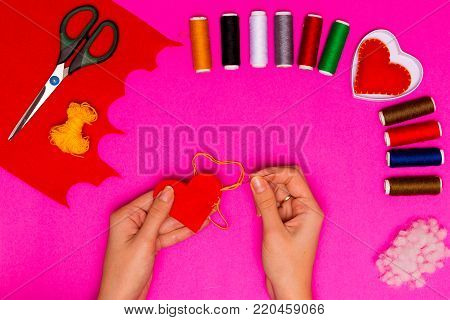 Woman's hands sew a pillow in the form of a heart on a pink table. Valentine background with handmade sewed pillow hearts in woman's hands. Happy lovers day