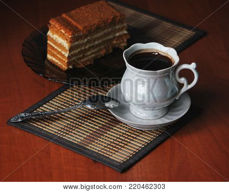 A cup of coffee and a slice of cake on a plate, delicious dessert,  layered cake