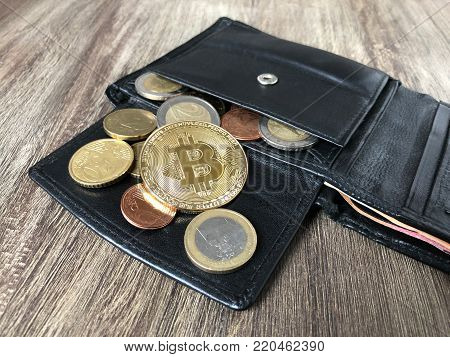 black leather wallet with bitcoin euro and cent coins, selective focus, cryptocurrency concept