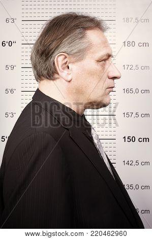 Older man portraited on police station in front of mug board