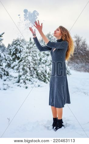 Beautiful cute red-haired girl with a nice smile throwing snow in air in forest. Joy from a first snow in the forest. Good winter weather.