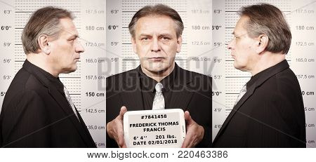 Criminal man portraited on police station in front of mug board with fake personal data