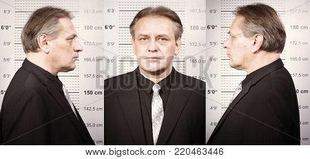 Criminal man portraited on police station in front of mug board