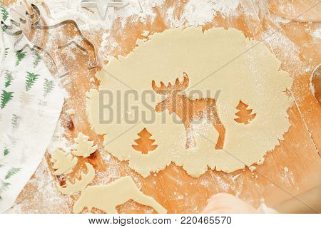 Deer and New Year tree cut on dough, Ready cookies of different shapes lie on wooden table, going to be baked. Hand made delicious pastry. Christmas cookies