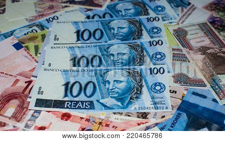The Brazilian currency on a pile with a different world currency.