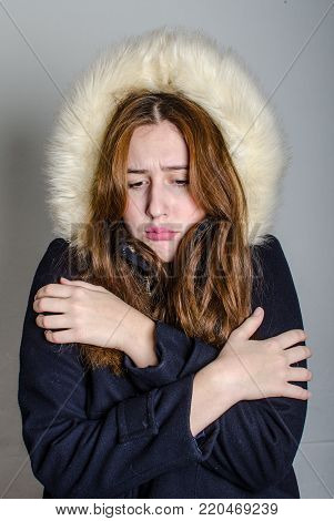 young woman shivering with winter in a fur coat