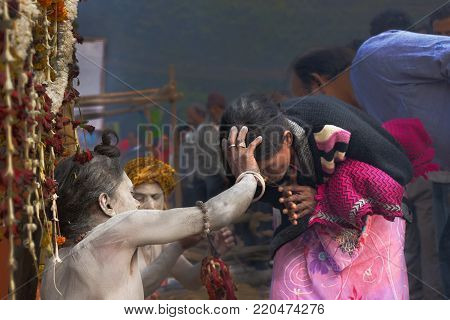 BABUGHAT, KOLKATA, WEST BENGAL / INDIA - 11TH JANUARY 2015 : Hindu Sadhu with white ash applied on body and face, blessing pink coloured dress clad Indian devotee woman.