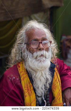 KOLKATA, WEST BENGAL, INDIA - JANUARY 11 TH 2015 : Portrait of an old Indian Sadhu with saffron dress and white beard on face.