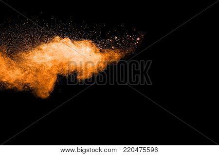 abstract orange powder explosion on black background. abstract orange dust splattered on  black background. Freeze motion of orange powder splash.