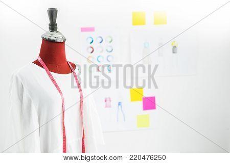 Asian tailor adjusts garment design on mannequin in workshop make a little adjustment to her work on model in the studio