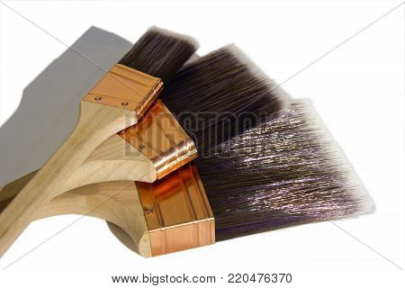 Three high quality synthetic paint brushes on a white isolated background.