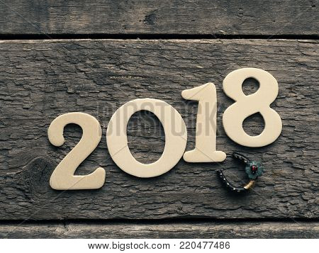 New Year 2018 with a horse shoe on a rustic wooden plank, Happy New Year and Good luck