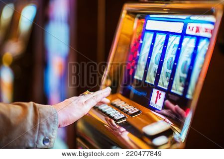 Casino Gambling Industry Theme. Caucasian Woman Playing Classic Slot Machine in the Casino.