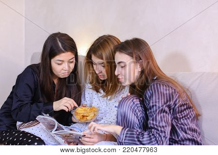Three wonderful women together hold fashionable women's magazine in their hands and read articles or view bright pictures, eat potato chips, chat and gossip, sitting on gray sofa in bright bedroom at night.