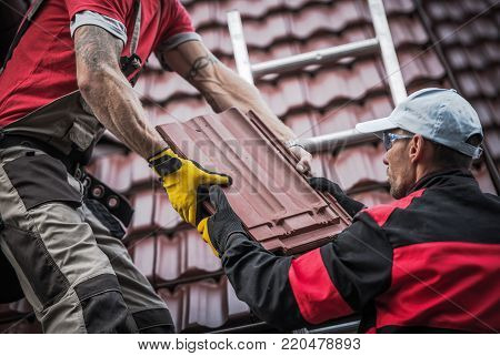 Red Roof Tiles Installation by Two Caucasian Roofers. Construction Industry Theme. poster