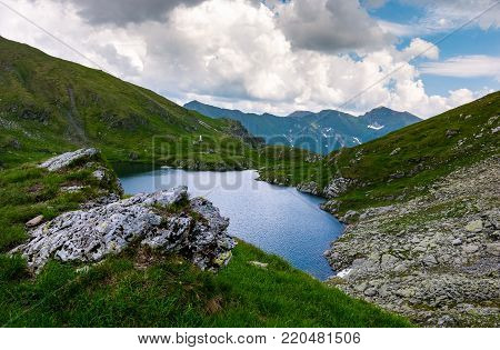 Capra glacier of Fagaras mountains of Romania. gorgeous summer landscape with beautiful sky. grassy hills with rocky cliff and some snow
