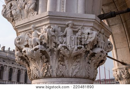 Detail of a column of the Doge's Palace on Piazza San Marco, Venice, Italy. Capital with plant ornament and cultural groups. Columns encircle the lower tier of the building.
