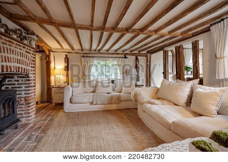 16th Century English cottage living room with cast iron fire beutifully decorated in pastel colours and furnishings with expose brick floor, expose brick chimney breast, beams and timbers, matching chairs and cushions.