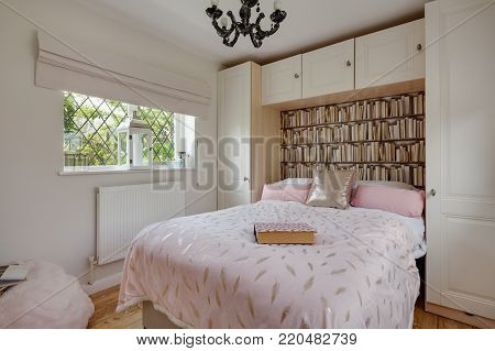 Modern stylish bedroom incorpoarting double bed within fitted a fitted range of wardrobes and cupboards, duvet, pillows, cushions and window looking into a wooded garden