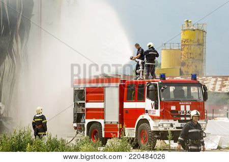 Sofia, Bulgaria - July 15, 2017: Firefighters extinguish fire disaster in a warehouse. Fire fighting in an industrial area.