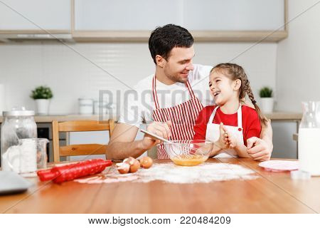 Affectionate brunet young male embraces daughter, sit together at kitchen, bake something delicious, prepare surprise for mother, surrounded with ingredients, mix eggs in bowl. Parenthood concept