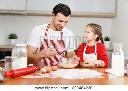 Curious female pretty child helps her father who mixes eggs, sit at kitchen, have pleasant conversation, enjoy togetherness. Little kids and her male parent bakes something delicious for party