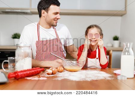 Cheerful brunet male wears apron looks at happy child who covers eyes with hearts, sit at wooden kitchen table, mixe eggs in bowl with whisk, have good time together. Family and childhood concept