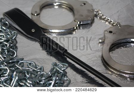 Detail on bdsm playful erotic selective focus objects, handcuffs, whip, chain on silver background