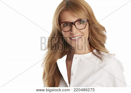 An attracive mature woman standing at isolated white background.