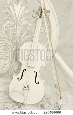 An old white violin of vintage style. Stringed musical instrument on a white forged chair