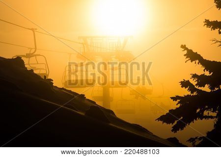 Chair ski lift with skiers sillhouettes at sunset
