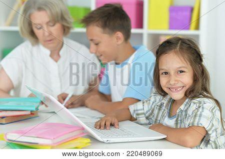 granny with her grandchildren doing homework together