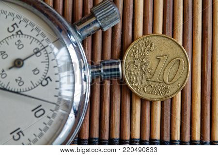 Stopwatch and coin with a denomination of ten euro cents on wooden table background