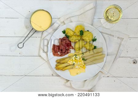 Asparagus dish with potatoes, ham, sauce and white wine from above on white painted wood, copy space