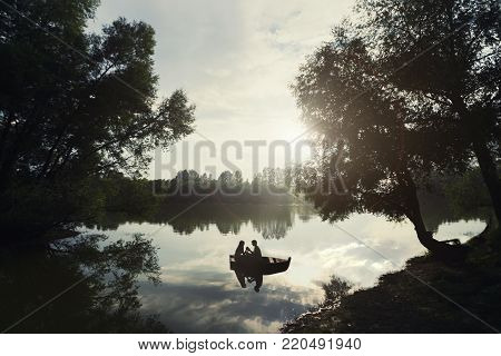 loving couple in a boat on the lake on sunset. silhouette