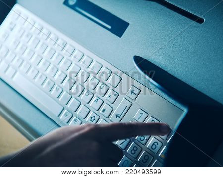 Modern filter over woman finger pressing the Pin Number button on the metallic keyboard of ATM Automatic Teller Machine to retrieve withdrawal money or use other finance  instrument