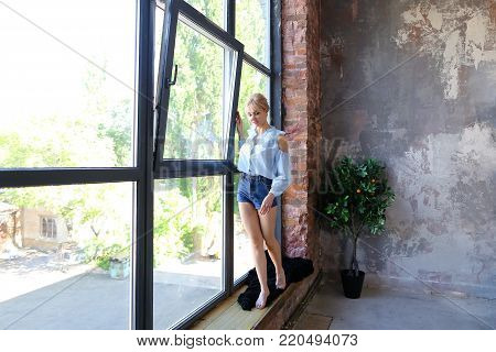 Sweet woman in excellent spirits and with smile on face poses and stands on windowsill near high panoramic window in spacious stylish bedroom with gray walls, bed and orange tree. girl of European appearance and gathered hair dressed in blue blouse