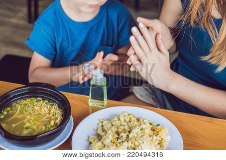 Mother And Son Using Wash Hand Sanitizer Gel In The Cafe