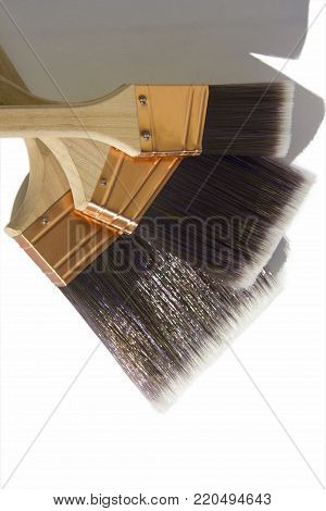 Three large synthetic high quality paint brushes on a white isolated background. poster