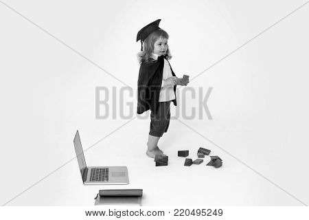 Small boy child with cute cheerful face in blue shirt black academic gown and squared cap standing playing with wooden cubes near notebook isolated on white background