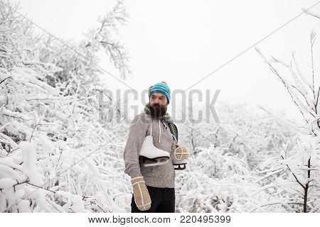 Winter sport and rest. Christmas. Temperature, freezing, cold snap, snowfall. skincare and beard care in winter. Man in thermal jacket, beard warm in winter. Bearded man with skates in snowy forest.