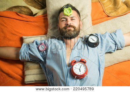 Time management, perfect morning. Relax and wake up, time. Tired hipster with clock. Man with clock in bedroom, loneliness. Bearded man sleep on floor with alarm clock.
