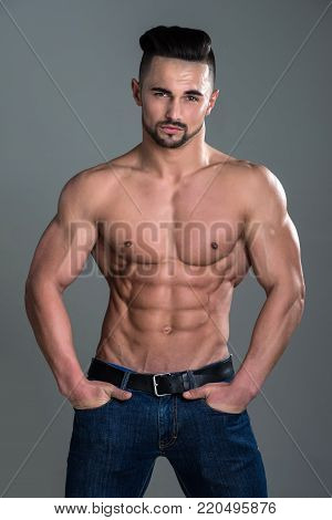 Athletic Bodybuilder Man On Grey Background.