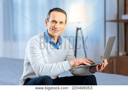 Technology lover. Pleasant middle-aged man sitting on the bed and posing with his laptop, smiling at the camera, while surfing the web