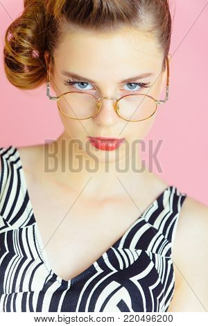 pinup, youth and look. secretary, hairdresser and cosmetics. Girl in stylish vintage dress on pink. Beauty and fashion, teacher. Woman with retro hair and fashionable makeup in glasses, pinup.
