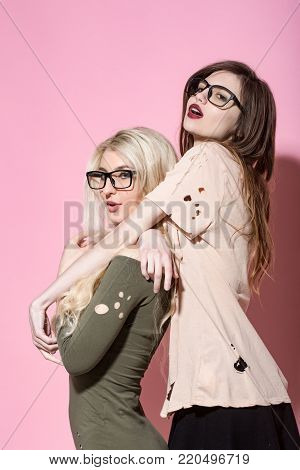 Visage, makeup, hairstyle. Girls pose in torn clothes on pink background. Beauty, look concept. Fashion, style, vogue. Women with long hair in geek glasses.
