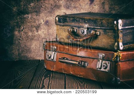 Fragment of old leather suitcases on wooden table. Processing in vintage style. The concept of travel.