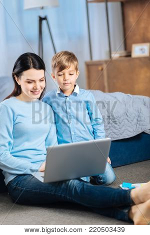 Interesting cartoon. Upbeat young woman and her little son sitting on the bedroom floor and watching cartoon together on the laptop