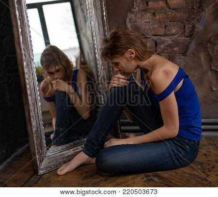 Beaten young woman victim of domestic violence and abuse sits on floor near mirror with bruises and wounds on her face and hands. Сoncept of domestic violence, sexual violence and cruelty.